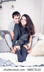 Happy Smiling Couple in love. Valentine's day. Winter portrait. Handsome young man and beautiful woman on a date spending time together at home scandinavian style.  Romance, family and love concept.