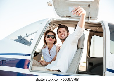 Happy smiling couple making selfie with smartphone inside plane cabin after landing