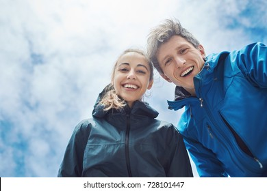 happy smiling couple, man and woman travelers looking in the camera at the sky background. bottom view