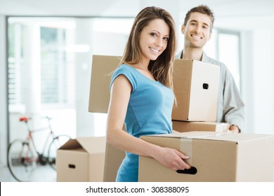 Happy smiling couple moving in a new house and carrying carton boxes, relocation and renovation concept