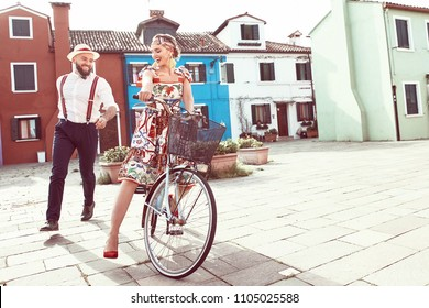Happy smiling couple near colorful houses in Burano Island, Venice, Italy. Woman dresses in colorful romantic dress, headband, riding bike, man in white shirt, linen hat and pants with suspenders