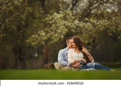Happy Smiling Couple Relaxing on Green Grass.Park.Young Couple Lying on Grass Outdoor. Elegantly dressed