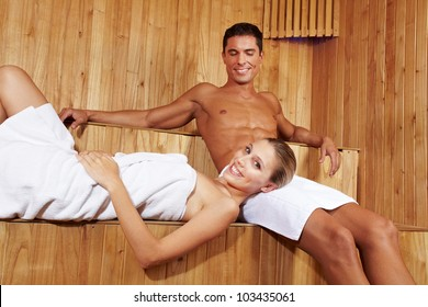 Happy smiling couple relaxing together in a sauna