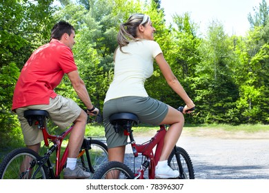 Happy smiling couple  riding  in the park