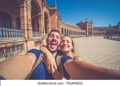 happy smiling couple take photo selfie in Spain square (plaza de espana) in Sevilla, Spain