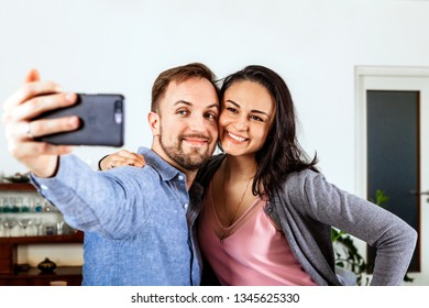 happy smiling couple taking selfie with a smart phone