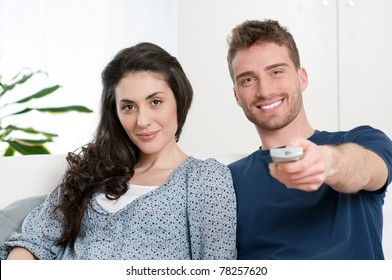 Happy smiling couple watching television at home