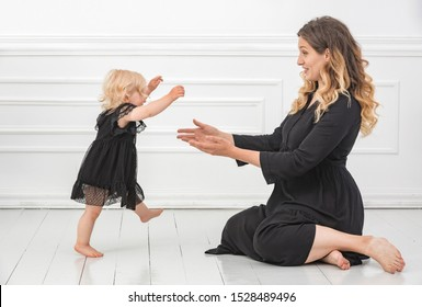 Happy smiling cute little baby girl wearing black dress doing her first steps walking to his mother in a white sunny living room.