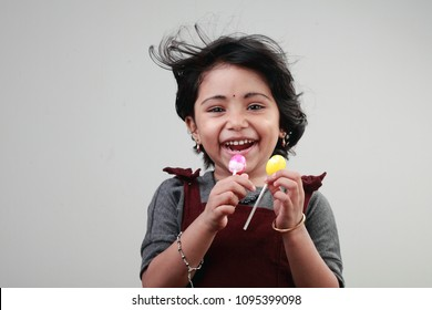 Happy smiling cute little girl with two lollypop