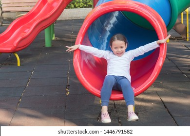 Happy smiling cute little girl playing in kid playground