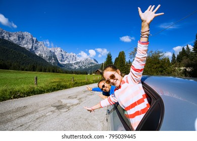 happy smiling dad and daughter looking out the car window and mountains in the background. Dolomites, Italy