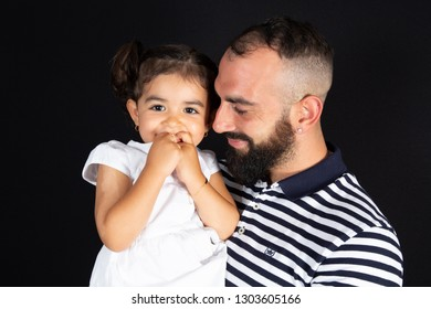 happy smiling daughter in father arms on black background