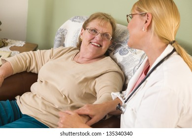 Happy Smiling Doctor or Nurse Talking to Senior Woman in Chair.