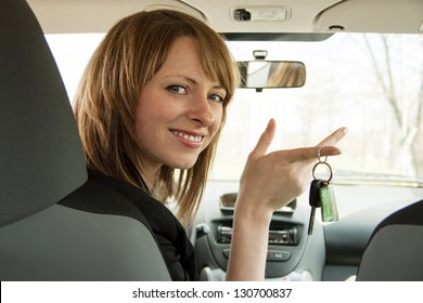 Happy smiling driver woman looking back and showing car key sitting in new auto