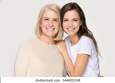 Happy smiling elder mother and millennial daughter posing for portrait. Laughing caring granddaughter embrace grandmother. Studio headshot isolated on gray background. Family, relatives, relationships