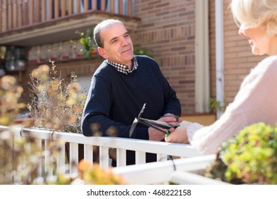Happy smiling elderly woman and aged man drinking tea in patio