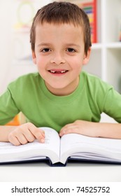 Happy smiling elementary school boy with missing tooth practice reading