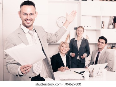 Happy smiling entrepreneur with papers standing in office with colleagues behind