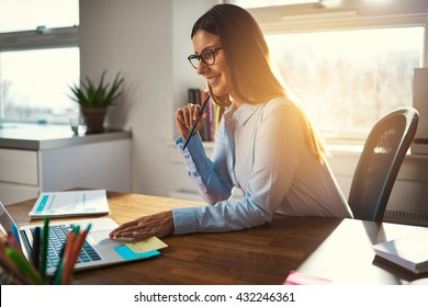 Happy smiling entrepreneur using laptop with pen in mouth looking concentrated