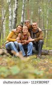 Happy smiling family in autumn forest sitting