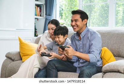 Happy and smiling , family- father, mother and son playing a video game at home.