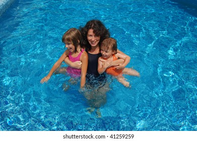 Happy smiling family with kids having fun in swimming pool