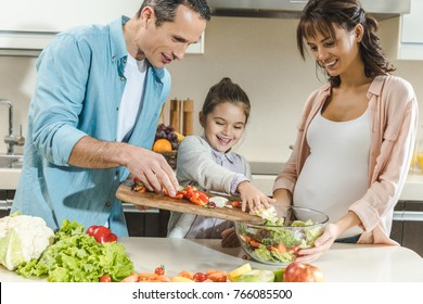 happy smiling family making salad together at kitchen