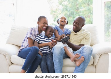Happy smiling family on the couch in the living room. Social distancing and self isolation in quarantine lockdown for Coronavirus Covid19