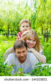 Happy Smiling Family in a park, lying on a grass