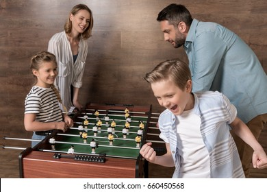 Happy smiling family playing foosball together
