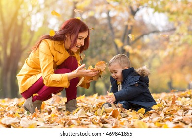 Happy smiling family playing with leaves in the park