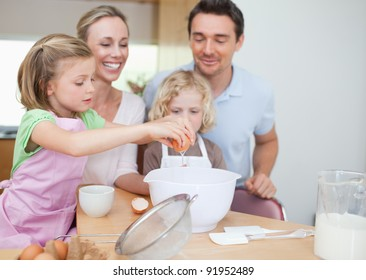Happy smiling family preparing dough together