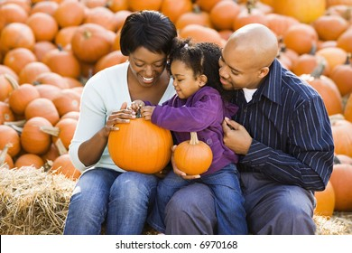 Happy smiling family sitting on hay bales and holding pumpkins at outdoor market.