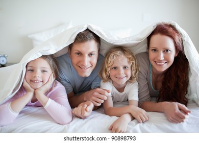 Happy smiling family under bed cover