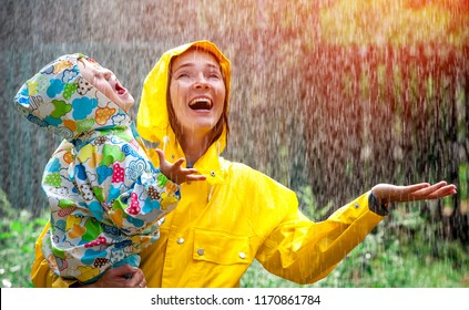 Happy smiling family under summer rain. Smiling mother and little child girl have fun time while playing outdoors under autumn shower. Kid without umbrella and in waterproof coat