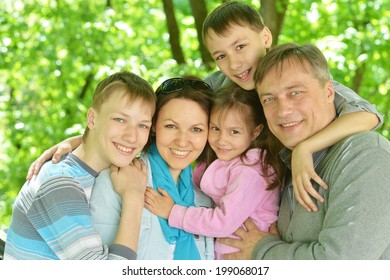 Happy smiling  family worth embracing in summer park