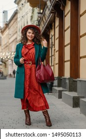 Happy smiling fashionable curvy woman wearing trendy autumn outfit: orange hat, snakeskin print midi dress, green coat, ankle boots, holding red wicker leather bag, posing in street of European city