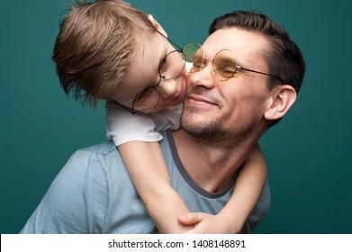 カジュアルTシャツとスタイリッシュな眼鏡を着た幸せな笑顔の父と子ども。父の日