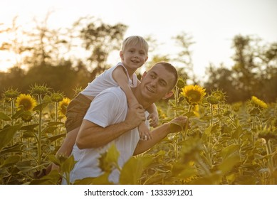 Happy smiling father with son on back walking on a green field of blooming sunflowers.