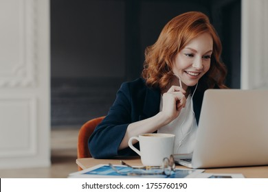 Happy smiling female entrepreneur has online conference via modern laptop computer, connected to wireless internet at home, uses earphones to hear interlocutor better, sits in coworking space