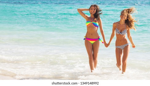 Happy smiling female friends walking in sea waves