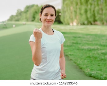 happy smiling female HEalth and nutrition Coach in white sportswear making fists