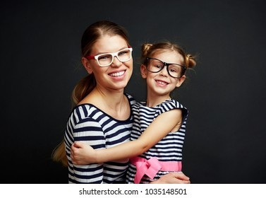 Happy smiling female with little girl changing eyeglasses with each other. Eye care concept.