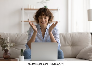 Happy smiling female pc user sit on couch splash hands in delight read good news on screen. Excited young woman enjoy perfect work of new browser app get positive answer from bank on request for loan