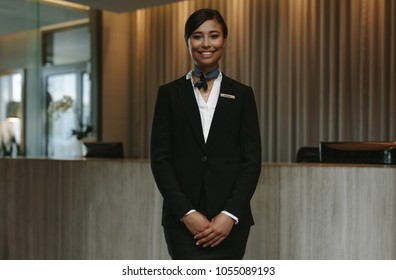 Happy smiling female receptionist in hotel. Beautiful concierge in uniform waiting for welcoming the guests.