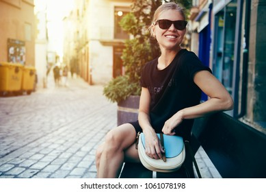Happy smiling female tourist sitting on bench on European street. Concept of vacation and lifestyle.