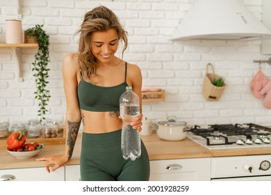Happy smiling fit woman in activewear  holding bottle of water and  posing in the kitchen  after fitness workout at home.
