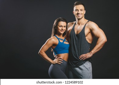 Happy smiling fitness couple on a black background.
