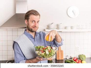 Happy smiling forty years old caucasian man making fresh vegetable salad in the kitchen (squeezing lemon juice for dressing). Healthy food and diet concept.