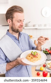 Happy smiling forty years old caucasian man or chef eating spaghetti bolognese in the kitchen - italian food.